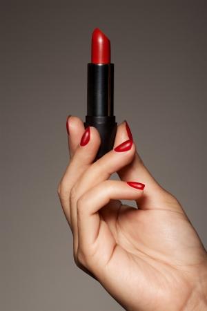 red tube: Mujer mano que sostiene el lápiz labial rojo
