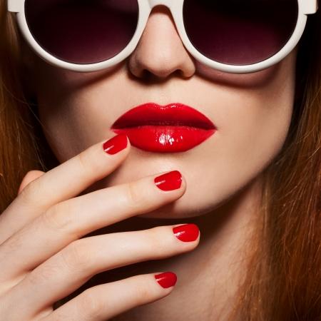 labios rojos: Mujer hermosa con maquillaje brillante y gafas de sol Foto de archivo