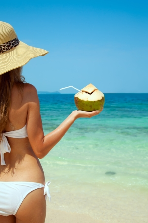 coconut drink: Young Woman Holding Fresh Cold Coconut At Tropical Beach Stock Photo