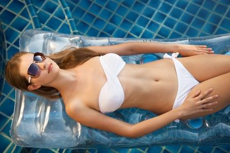 Beautiful woman sunbathing in swimming pool