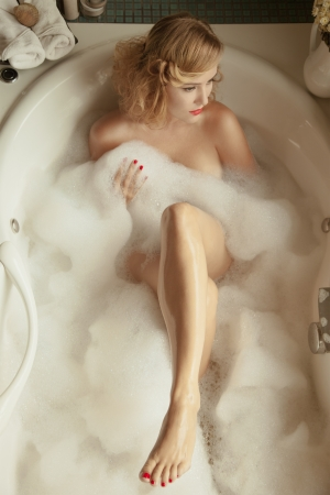 Portrait of elegant beautiful woman relaxing in a spa bath  photo