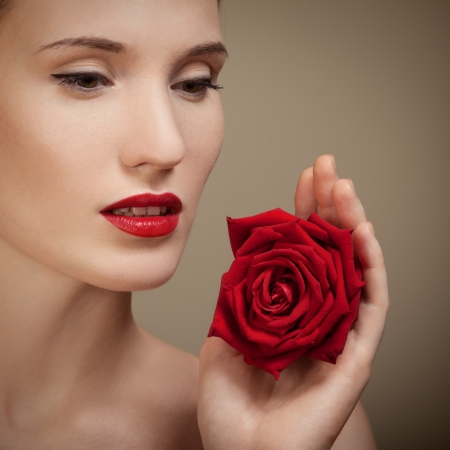 Beautiful Woman Holding Red Rose In Hand photo