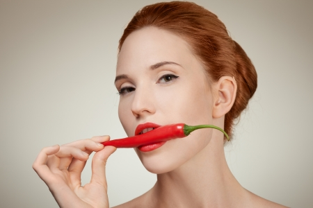 Portrait Of Beautiful Woman Biting Spicy Hot Red Cayenne Chili Pepper photo
