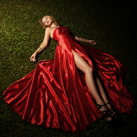 Beautiful Lady In Red Dress Lying On Green Grass photo