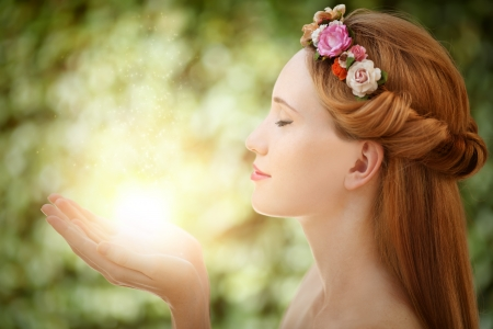 Beautiful fairy woman with glow in hands on natural green background Stock Photo