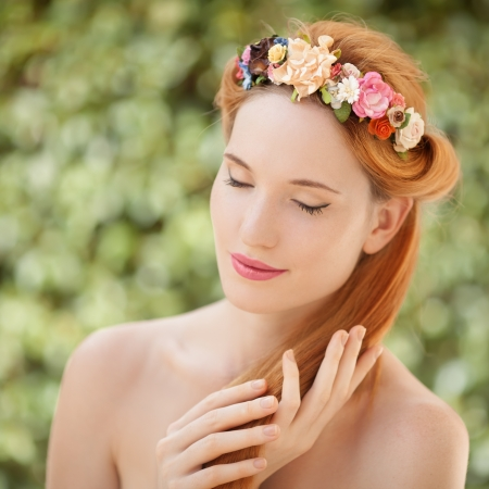 Beautiful young woman with flowers wreath in hair on natural green background photo