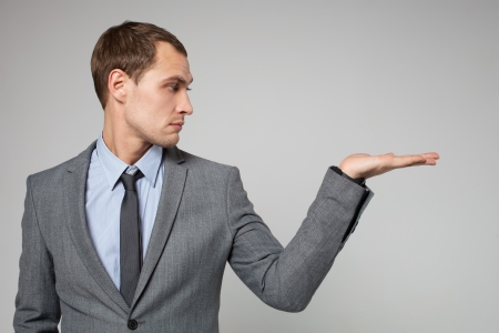 young business man holding something imaginary in his hand and looking at it photo