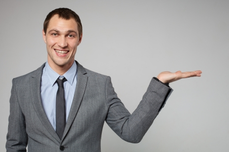something: young business man holding something imaginary in his hand Stock Photo