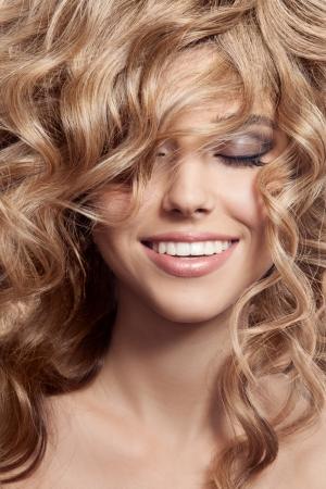Mujer sonriente hermosa. Saludable pelo largo rizado