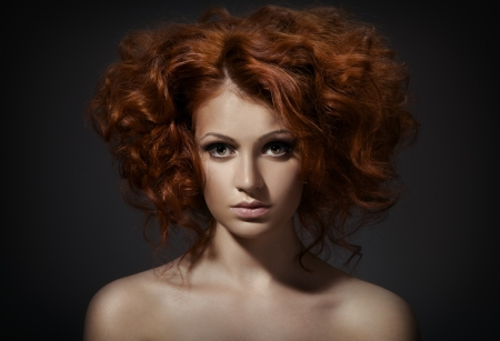 Beautiful woman with curly hairstyle against dark background