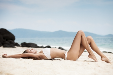 Young Woman Sunbathing At Tropical Beach photo
