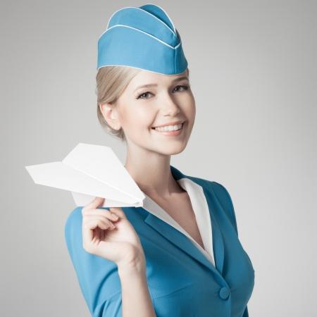 air hostess: H�tesse charmante holding papier avion dans la main. Fond gris. Banque d'images