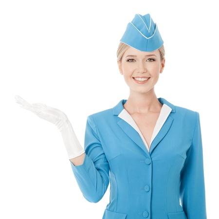 Charmante Stewardess gekleed in blauwe uniform houden in de hand op een witte achtergrond