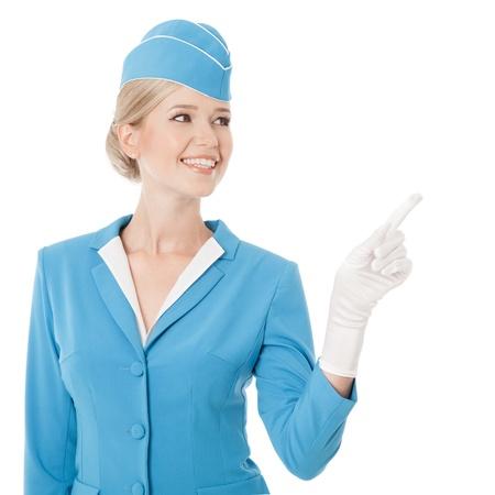 航空ショー: 白い背景の上に指を指して青い制服を着て魅力的なスチュワーデス 写真素材