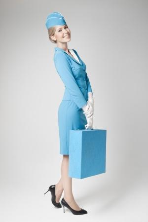 Azafata Encanto vestida de azul uniforme y maleta en el fondo gris photo
