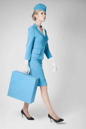 Charming Stewardess Dressed In Blue Uniform And Suitcase On Gray Background photo