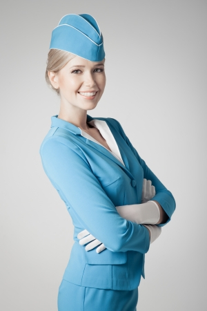 Charming Stewardess Dressed In Blue Uniform On Gray Background photo