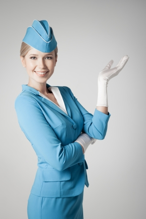 air hostess: Charming Stewardess Dressed In Blue Uniform Pointing On Gray Background Stock Photo