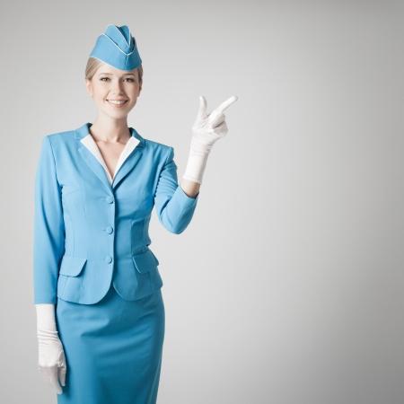 航空ショー: 灰色の背景で指を指している青い制服を着て魅力的なスチュワーデス