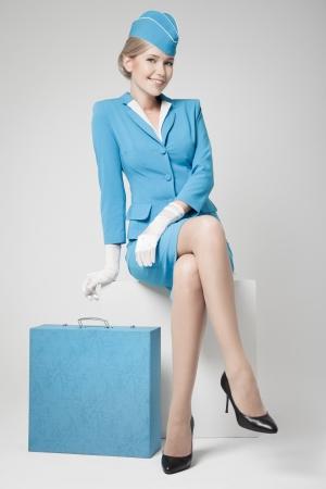 azafata: Azafata Encanto vestida de azul uniforme y maleta en el fondo gris