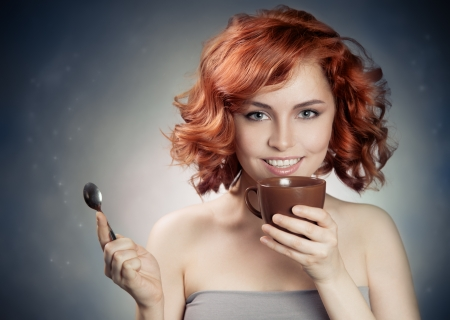 young pretty woman drinking coffee Stock Photo - 21976373