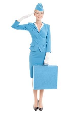 Hôtesse charmante habillée en uniforme bleu et valise sur fond blanc Banque d'images