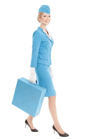 Charming Stewardess Dressed In Blue Uniform And Suitcase On White Background photo