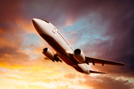 jetliner: Airplane in the sky at sunset Stock Photo