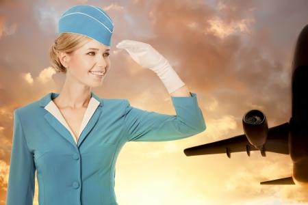 stewardess: Charming Stewardess Dressed In Blue Uniform On Sky Background