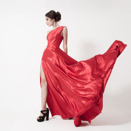 wind dress: Young beauty woman in fluttering red dress. White background.