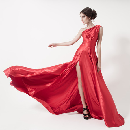 flyaway: Young beauty woman in fluttering red dress. White background.