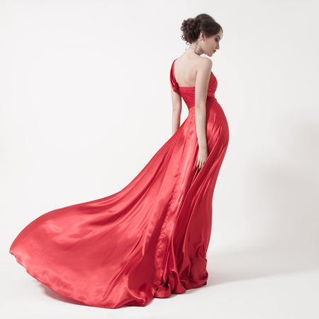 Mujer joven de la belleza en el aleteo vestido rojo. Fondo blanco.