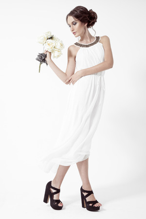 Young brunette woman and white roses. White Background. Stock Photo