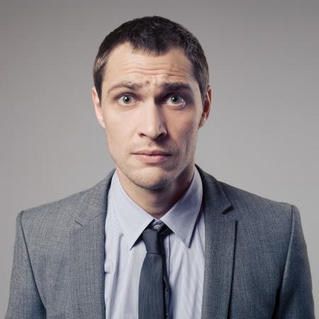 stupor: Confused Businessman On Gray Background