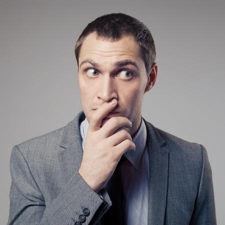 desconfianza: El hombre de negocios Confundido En Fondo Gris
