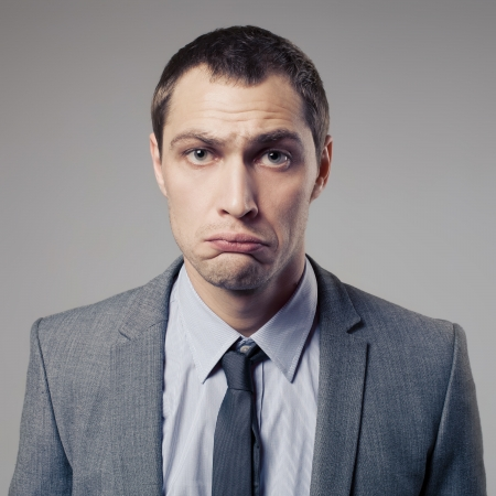perplexity: Confused Businessman On Gray Background