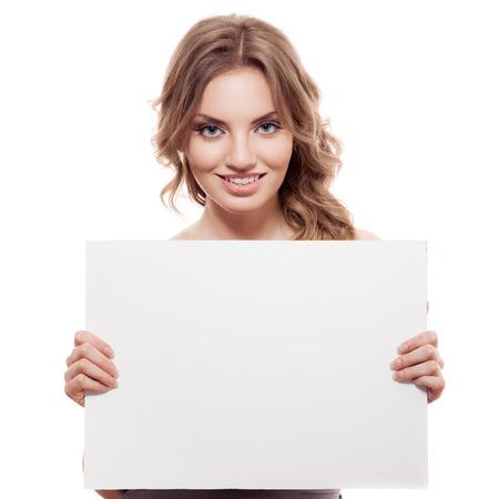 vrouw blond: Portret van een vrolijke jonge blonde vrouw die een witte lege banner. Geïsoleerd