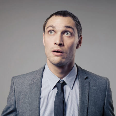 clueless: Confused Businessman On Gray Background