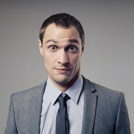 confused face: Confused Businessman On Gray Background