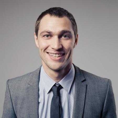 pleasant: Pleasant businessman portrait on grey background Stock Photo