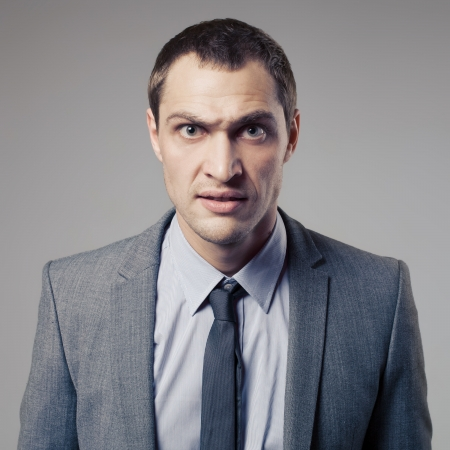 distraught: Angry Businessman On Gray Background Stock Photo