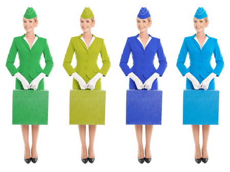 stewardess: Charming Stewardess Dressed In Uniform And Suitcase With Color Variants. Isolated On White Background. Stock Photo
