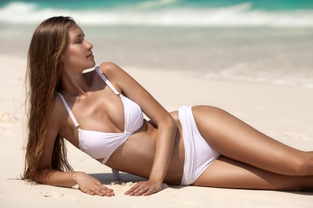 Young Woman Sunbathing At Tropical Beach Stock Photo