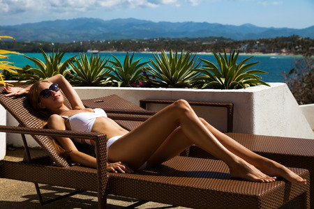 sunbed: Young woman lie on sunbed and sunbathing. Luxury sea view.