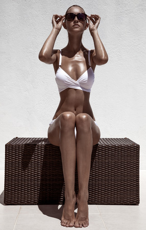 Beautiful tan female model posing in bikini and sunglasses. Against white wall. Stock Photo