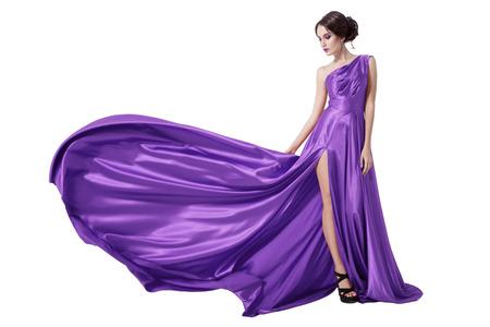 舞う紫ドレスの若い美しさの女性。白い背景で隔離されました。