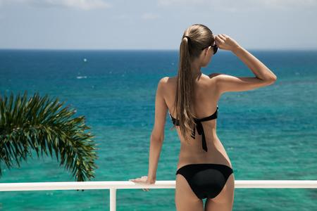 젊은 여성이 일광욕. 럭셔리 바다 전망.