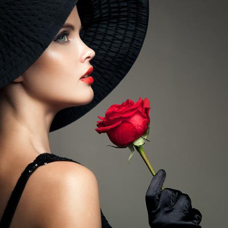 nude young: Красивая женщина с красной розой. Ретро мода изображения. Фото со стока