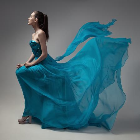舞う青いドレスのファッションの女性。灰色の背景。 写真素材