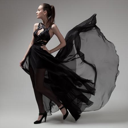 펄럭이는 검은 드레스 패션 여자. 회색 배경입니다.